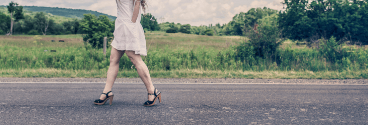 Woman in white dress and heels walking down a country road