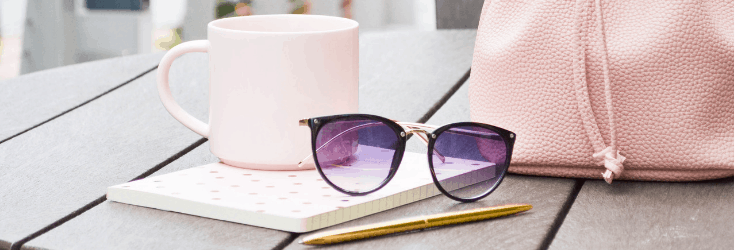 Sunglasses, a mug and a purse on a table
