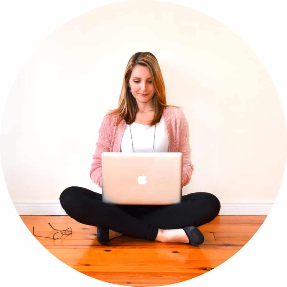 Woman Sitting cross legged on hardwood floor with laptop Apple computer on her lap