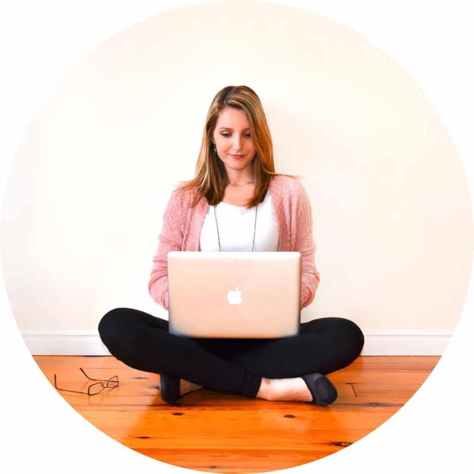 Woman Sitting cross legged on hardwood floor with laptop Apple computer on her lap