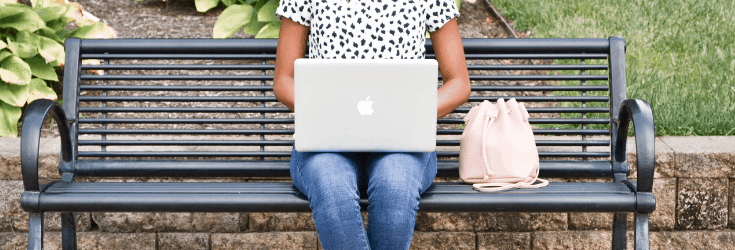 Woman sitting on a bench with a laptop computer on her lap