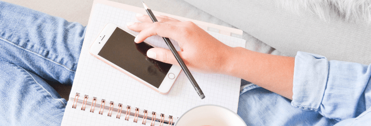 Woman's hand with iPhone and notebook on lap