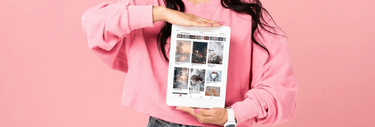 Woman in pink holding iPad with Pinterest Pins